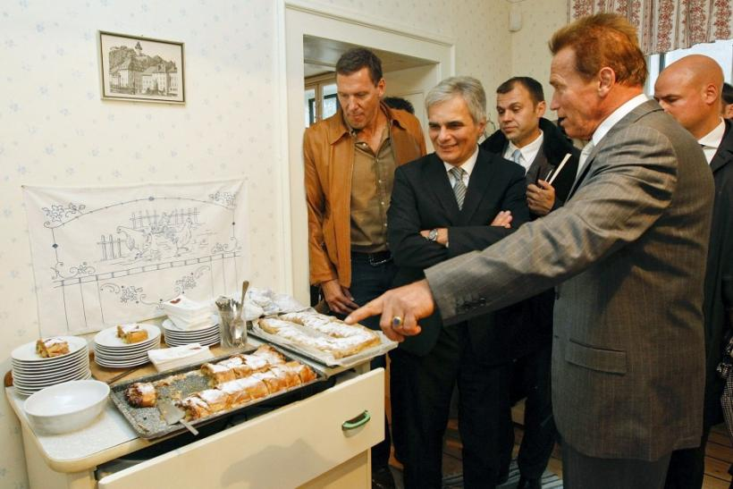 Austrian actor, former champion bodybuilder and former California governor Arnold Schwarzenegger (R) looks at apple strudel next to Austrian Chancellor Werner Faymann (2nd L) and German actor Ralf Moeller (L) as they tour inside Schwarzenegger's former ho