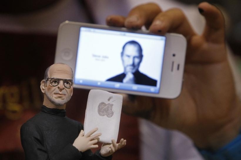 Artist Gennaro Di Virgilio holds an iPhone as he displays a model figure of Apple founder Steve Jobs in his shop in Naples