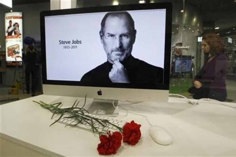 Carnations are placed before a computer screen showing a portrait of Apple co-founder and former CEO Steve Jobs at an Apple store in St. Petersburg