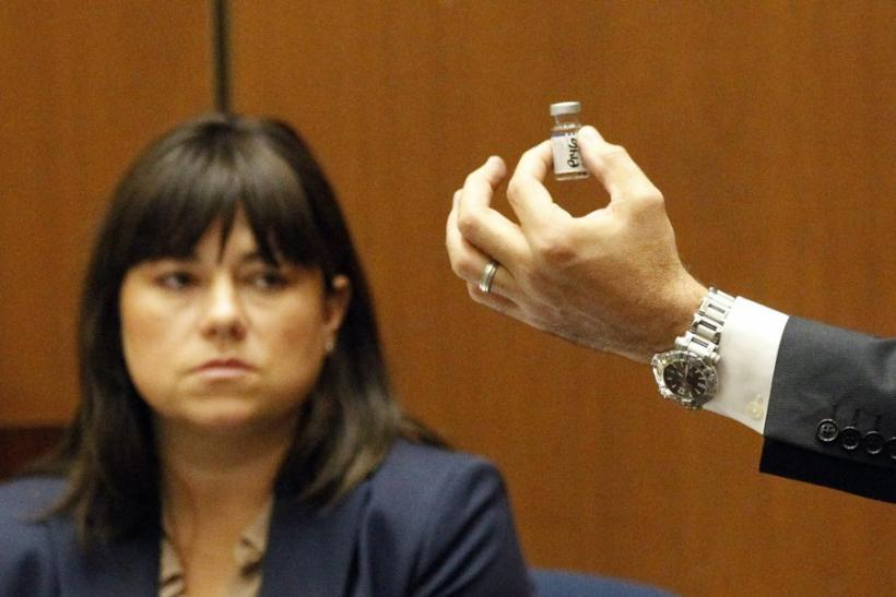 Deputy District Attorney David Walgren holds a bottle found by Los Angeles County coroner investigator Elissa Fleak (L) during her testimony at Dr. Conrad Murray's trial in pop star Michael Jackson's death in Los Angeles