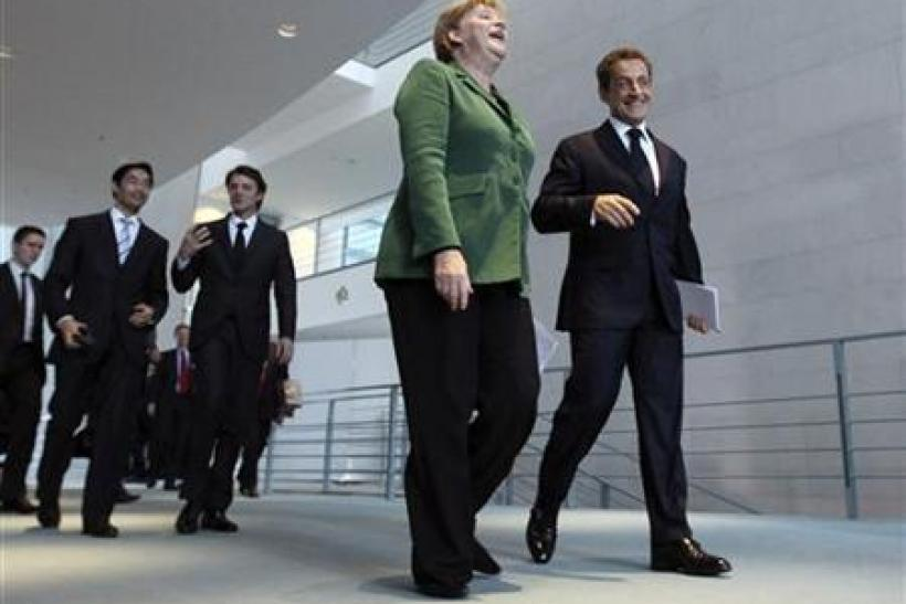 French President Sarkozy and German Chancellor Merkel arrive to address a news conference at the Chancellery in Berlin
