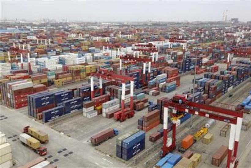 Trucks are driven into a shipping container area at Qingdao port