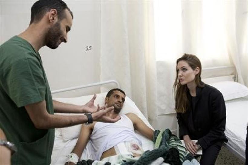 Actress and U.N. goodwill ambassador Angelina Jolie (R) visits a patient in a hospital in Misrata during her Libya visit