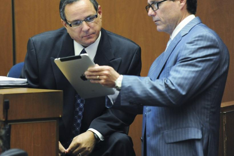 Scott Smith reads notes from Ed Chernoff's iPad during Dr. Conrad Murray's trial in the death of pop star Michael Jackson in Los Angeles