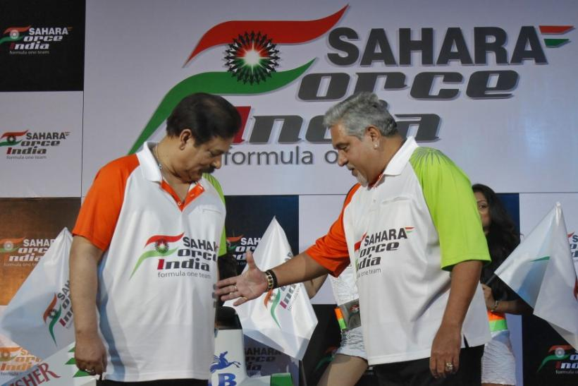 Vijay Mallya, co-owner of the Force India Formula One team, extends his hand to Sahara Group Chairman Subrata Roy at a news conference in New Delhi