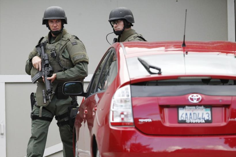Security personnel perform yard-to-yard searches during a manhunt in Sunnyvale