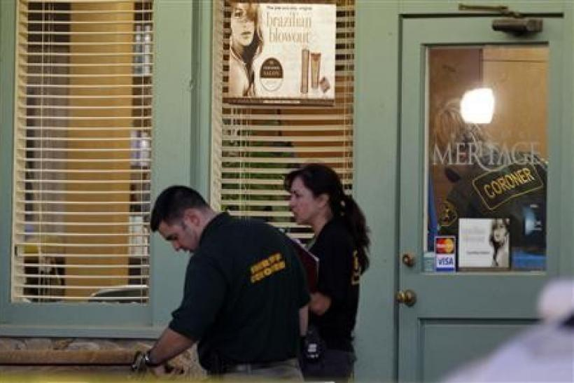 An Orange County Coroner and crime scene investigators process bodies for removal from Salon Meritage, in Seal Beach, California