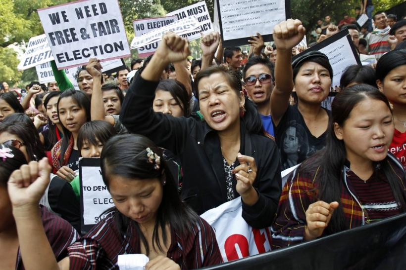 Burmese demonstrators hold a placard and shout slogans during a protest in New Delhi