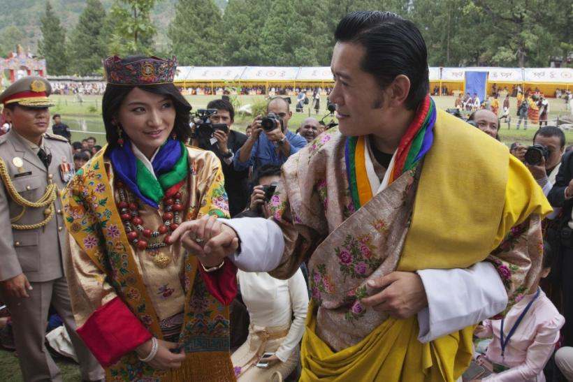 King Jigme Khesar Namgyel Wangchuck (R) holds hands with Queen Jetsun Pema while greeting villagers in Bhutan's ancient capital Punakha