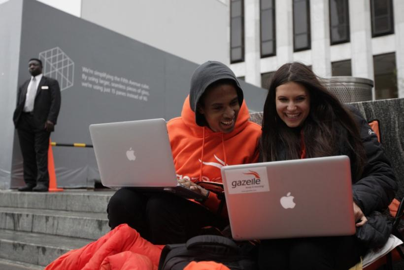 Keenen Thompson and Jessica Mellow surf the web while waiting in line to buy an iPhone 4S at the Apple Store on 5th Avenue in New York