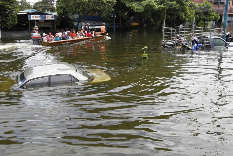 Residents travel by boat on a flooded street in Ayutthaya province