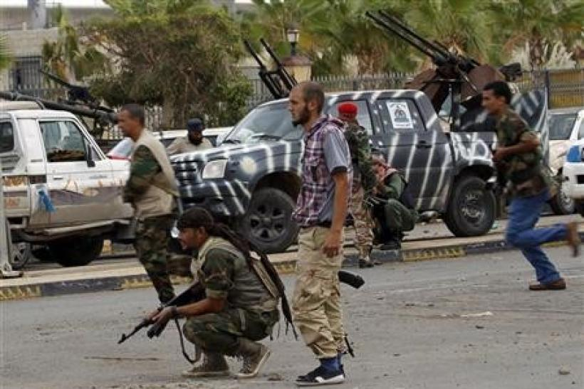 Anti-Gaddafi fighters take cover during clashes with pro-Gadhafi forces at the front line in the center of Sirte