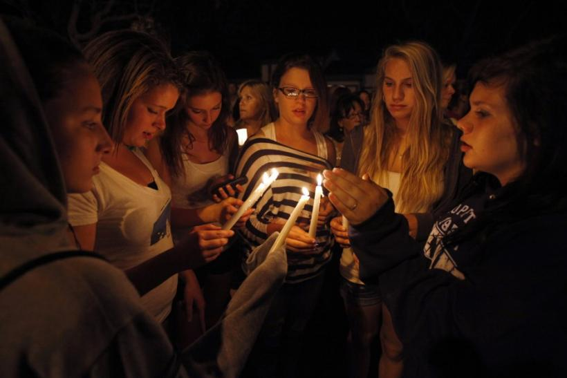 Mourners hold a candlelight vigil at the Salon Meritage hair salon in Seal Beach