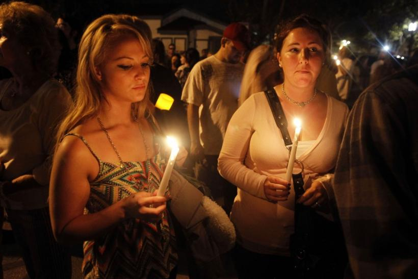 Kelsei Allan and Kaitlin Sallade of Seal Beach attend a candlelight vigil, one day after a gunman killed eight people in a shooting rampage at Salon Meritage, in Seal Beach, California