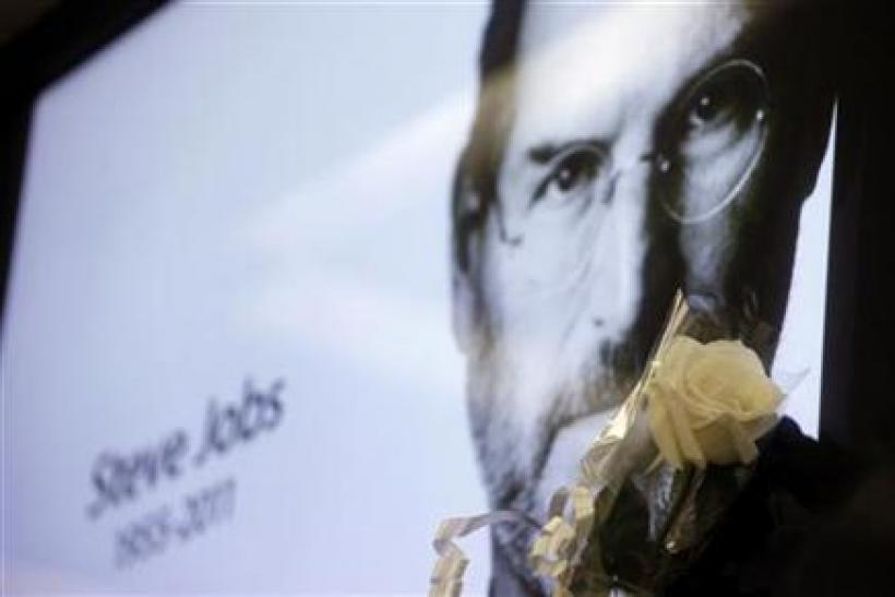 A flower is seen next to a portrait of Apple co-founder and former CEO Steve Jobs at Apple's store in Sao Paulo