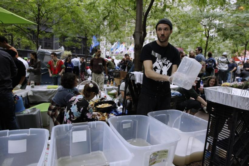 A member of the Occupy Wall Street movement cleans dishes in Zuccotti Park near the financial district of New York