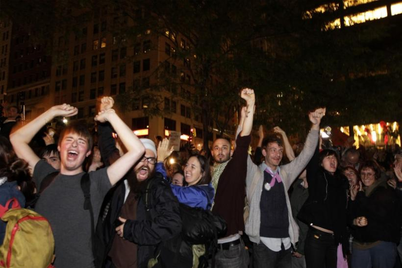 Members of the Occupy Wall St movement react after an announcement that a planned cleaning has been suspended in Zuccotti Park, near the financial district of New York