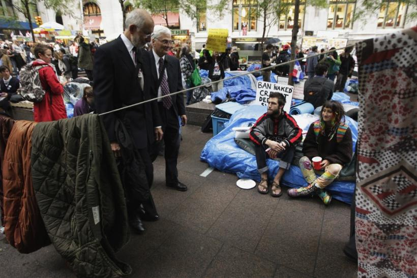 Men dressed in suits walk past members of the Occupy Wall Street movement as sleeping materials hang on a clothes line in Zuccotti Park near the financial district of New York