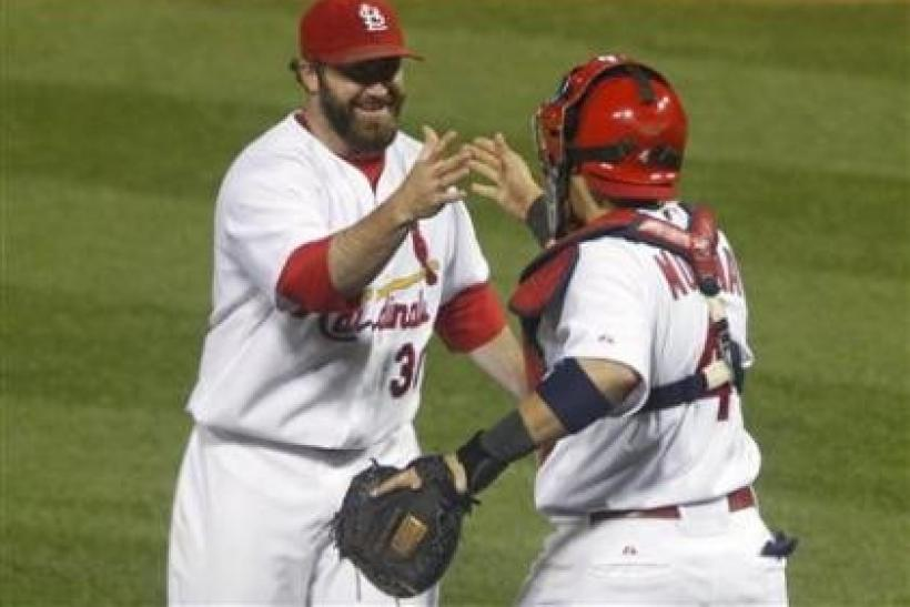 St. Louis Cardinals pitcher Jason Motte (L) and catcher Yadier Molina congratulate each other after beating the Milwaukee Brewers in Game 5 of the MLB NLCS baseball playoff game in St. Louis, Missouri