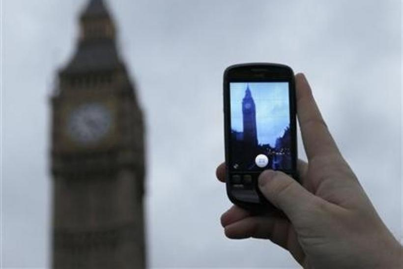 A man holds up a mobile phone in central London