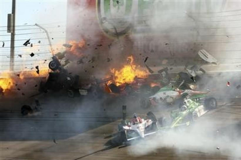 The race car of driver Will Power (L) hits the wall along with drivers J.R. Hildebrand (C) and Charlie Kimball (R) during the IZOD IndyCar World Championship race at the Las Vegas Motor Speedway