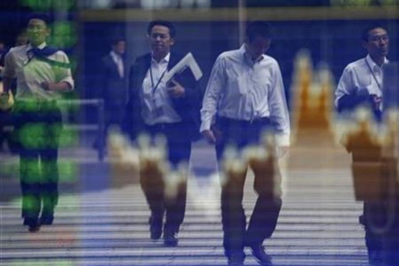 Pedestrians are reflected in a screen displaying the stock index prices in Tokyo
