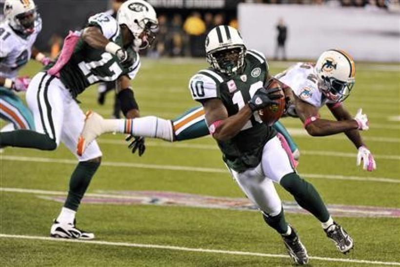 New York Jets receiver Santonio Holmes (front R) runs for a touchdown after catching a pass from quarterback Mark Sanchez during the fourth quarter of their NFL game against the Miami Dolphins in East Rutherford, New Jersey October 17, 2011. At back are J