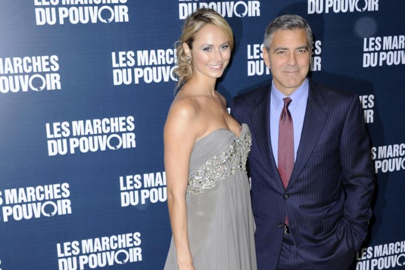 "Director and cast member George Clooney (R) and actress Stacy Keibler pose for photographers as they arrive for the premiere of his film ""The Ides of March"" in Paris"