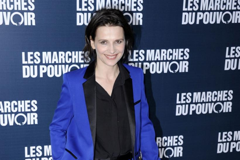 "Actress Juliette Binoche poses for photographers as she arrives for the premiere of the film ""The Ides of March"" directed by George Clooney in Paris"