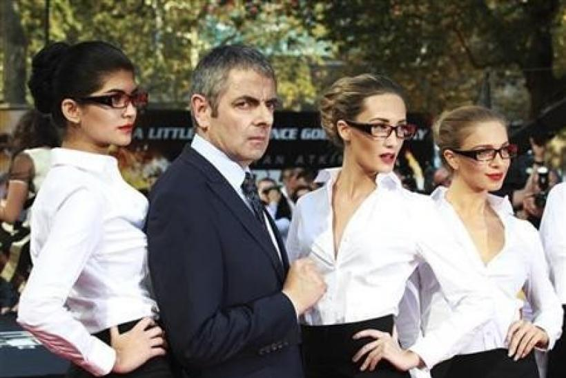 Actor Rowan Atkinson poses for a photograph with models as he arrives for the UK premiere of Johnny English Reborn, at the Empire Leicester Square in central London