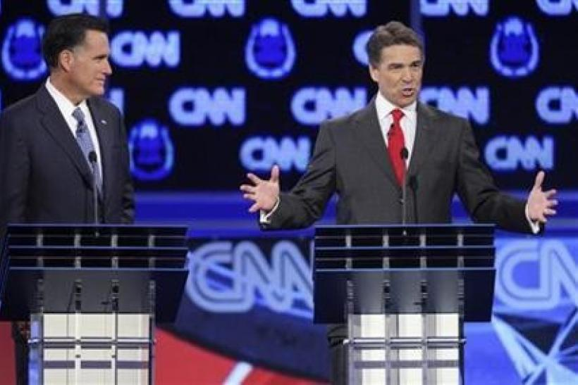 Texas Governor Rick Perry (R) speaks as former Massachusetts Governor Mitt Romney listens as they take part in the CNN Western Republican debate in Las Vegas, Nevada