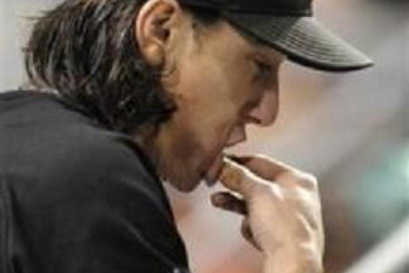 San Francisco starting pitcher Tim Lincecum (55) puts some chewing tobacco in his mouth during the 11th inning against the Pittsburgh Pirates in their MLB National League baseball game in Pittsburgh, Pennsylvania