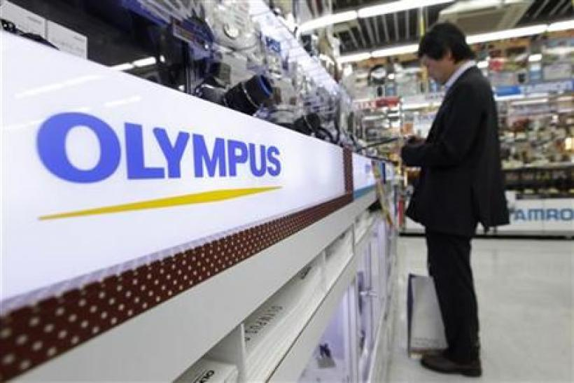 A man looks at Olympus digital cameras at an electronics store in Tokyo