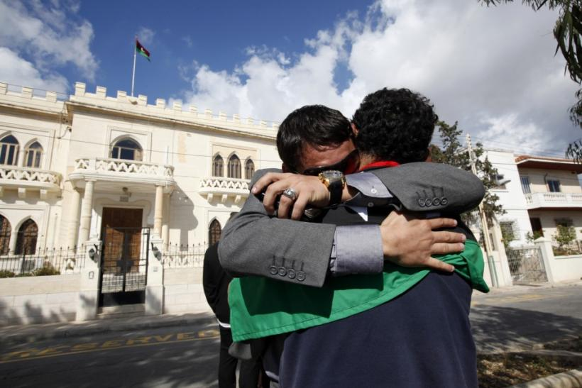 Libyan nationals in Malta embrace after hearing news that Libyan leader Muammar Gaddafi has been killed in Sirte, outside their embassy in Balzan