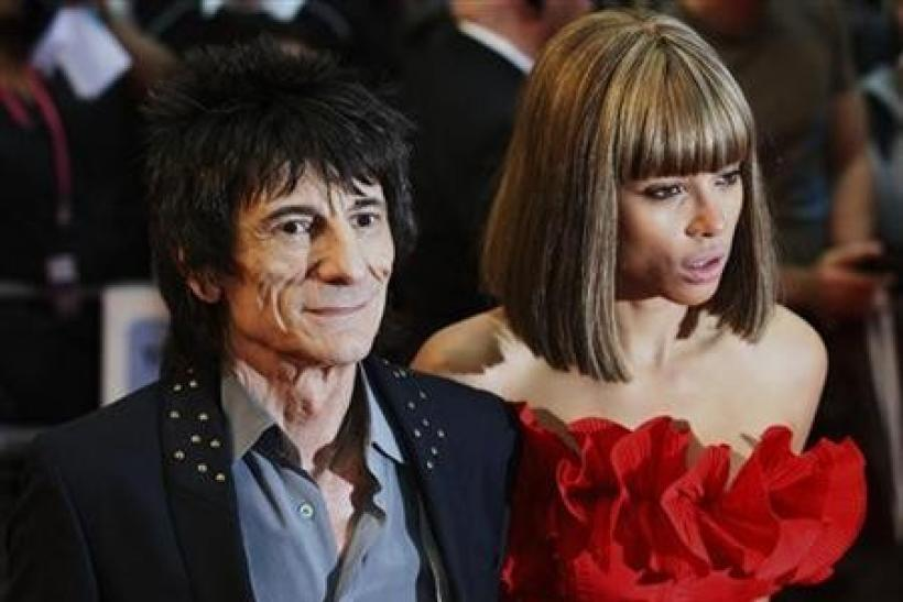 Rolling Stones guitarist Ronnie Wood and Ana Araujo pose for photographers as they arrive for the world premiere of the film Larry Crowne at Westfield in west London