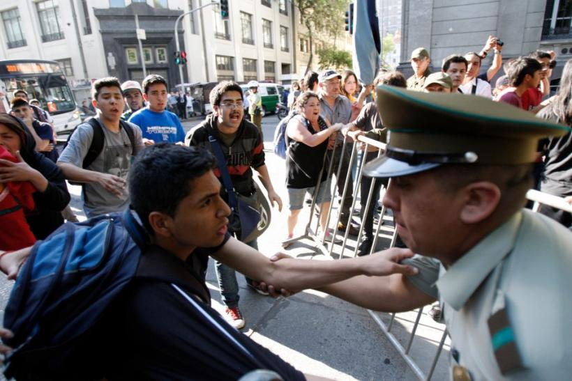 Demonstrators clash with riot police during a protest in Santiago