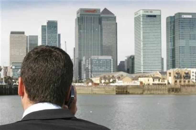 A man speaks on his mobile phone while standing on a boat on the River Thames with Canary Wharf and the financial district of London seen in the background.