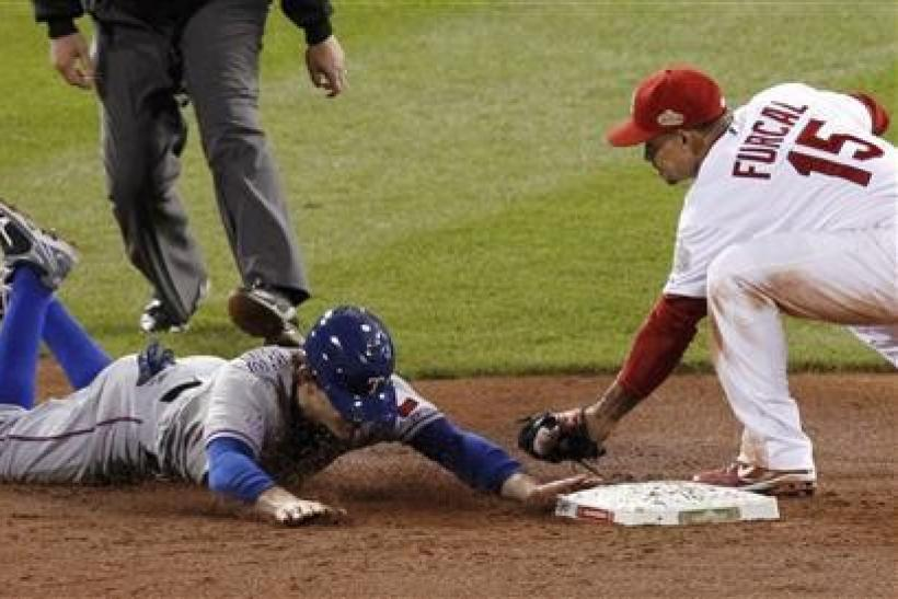 Texas Rangers second baseman Ian Kinsler steals second base on St. Louis Cardinals shortstop Rafael Furcal in the ninth inning in Game 2 of MLB's World Series baseball championship in St. Louis, Missouri