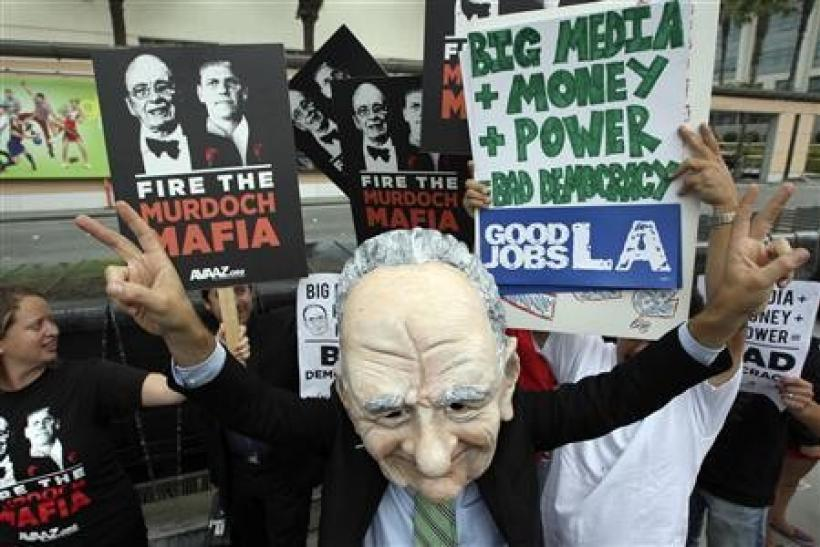 Brent Olson wears a puppet head representation of Rupert Murdoch as protesters demonstrate at Fox Studios during the annual News Corp. stockholder meeting in Los Angeles, California