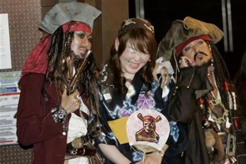 A woman takes a picture with participants who are dressed as ''Captain Jack Sparrow'', a character from ''Pirates of the Caribbean: At World's End'', at a costume event to promote the movie in Tokyo