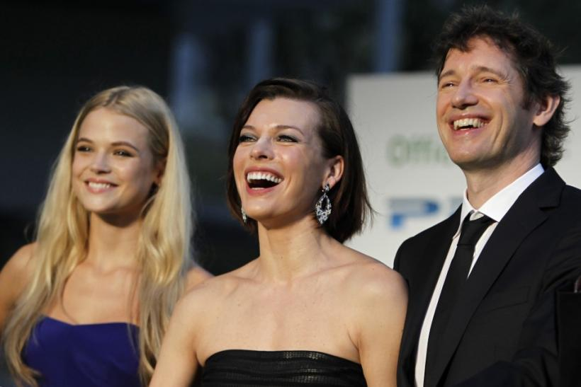 Cast members Milla Jovovich (C) and Gabriella Wilde (L), together with director Paul W. S. Anderson, poses during a photo session at the Tokyo International Film Festival