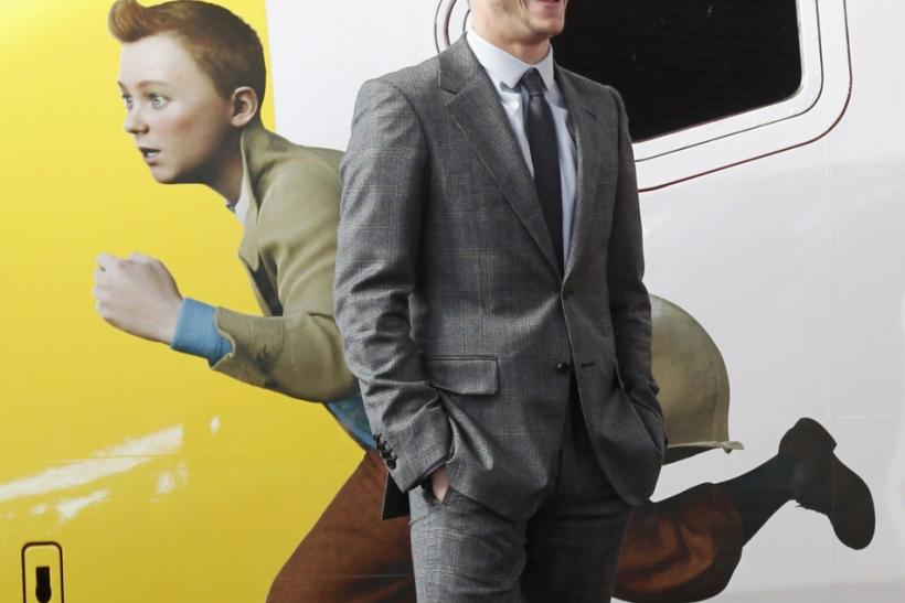 Actor Jamie Bell stands next to a figure of Tintin painted on a Thalys high-speed train in Brussels