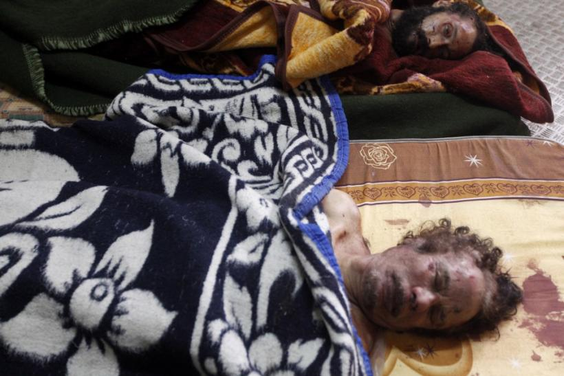 Dead bodies of Gaddafi and his son are displayed inside a metal storage freezer in Misrata