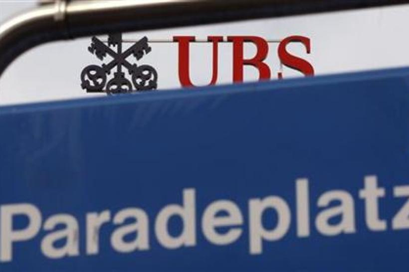 The logo of Swiss bank UBS on the roof of the company's headquarters is seen behind a road sign at the Paradeplatz square in Zurich