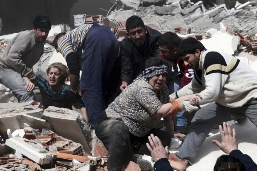 Rescue workers rescue people trapped under debris after an earthquake in a village near the eastern Turkish city of Van