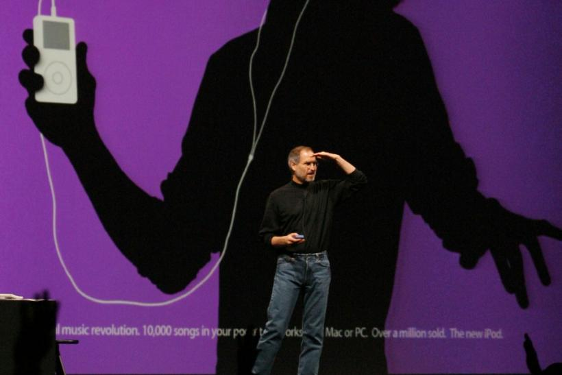 Apple CEO Steve Jobs looks out over the crowd as a new television commercial for Apple iPod digital music is displayed behind him, at the 2004 Macworld Conference and Expo in San Francisco, January 6, 2004.