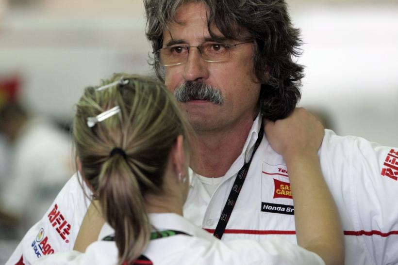 Paolo, the father of Marco Simoncelli of Italy, is consoled at the pit during the Malaysian Grand Prix in Sepang