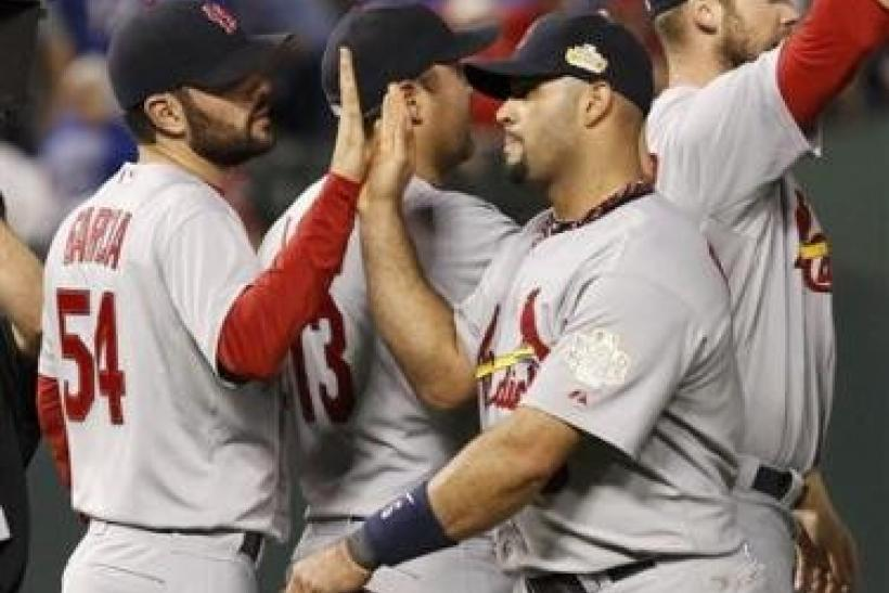 St. Louis Cardinals first baseman Albert Pujols (C) slaps hands with starting pitcher Jaime Garcia (54) after defeating the Texas Rangers in Game 3 of MLB's World Series baseball championship in Arlington, Texas