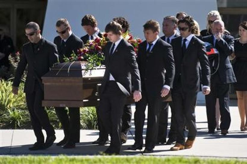 Pallbearers, including IndyCar drivers Tony Kanaan (L), Scott Dixon (third L) and Dario Franchitti (4th R) carry the casket of fellow driver Dan Wheldon as they escort Susie Wheldon (3rd R), Clive Wheldon and Ashley Wheldon (R) from the church during a fu