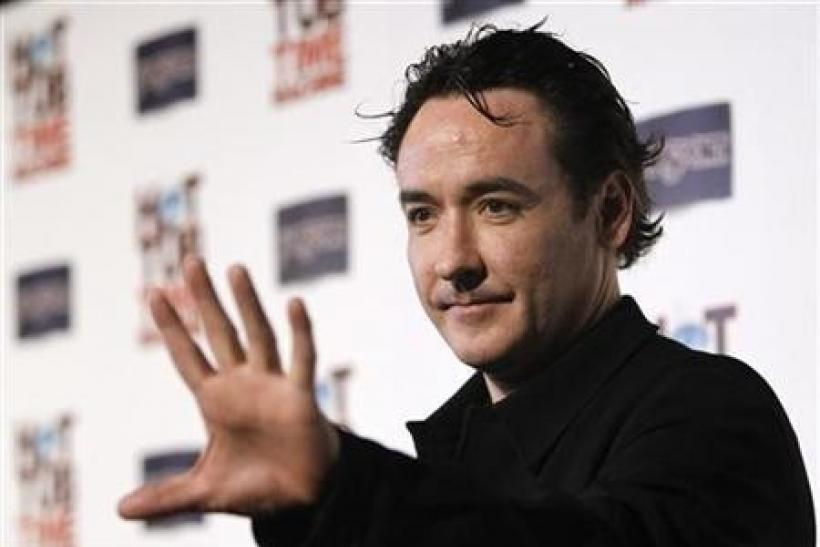 Cast member John Cusack waves at the premiere of ''Hot Tub Time Machine'' in Hollywood, California